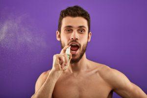 man using mouth spray